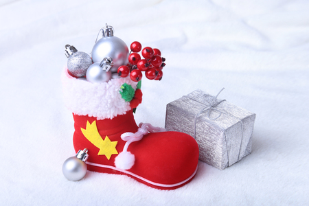 Merry Christmas composition. Santa's shoe with gift boxes on billowy feathers with snow and snowflakes. Happy holidays