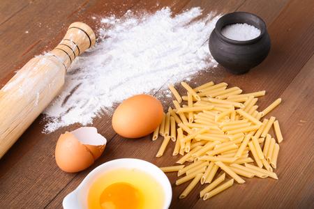 egg, flour, salt ingredients for pasta penne bolognese. Cooking concept. Top view. Banque d'images - 115570643