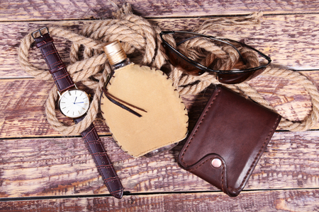 Stylish mens business accessories. Watch, wallet, bottle with cologne on wooden background.