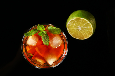 Glass of Dark Rum Cocktail with lime, orange, ice cubes and mint leaves on black mirror background. Top view.