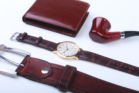 Mens accessories for business and rekreation. Leather belt, wallet, watch and smoking pipe on white background.. Top view composition.