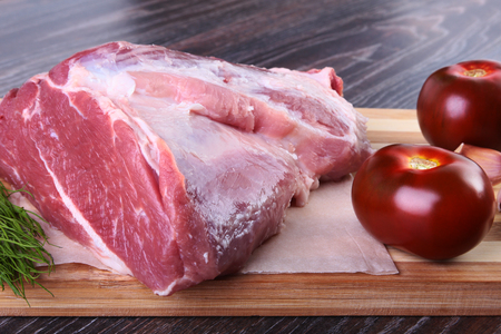 Raw pork steaks on wooden board with herbs, garlic, spices and tomatoes ready for cooking. Selective focus.