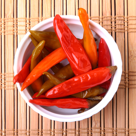 Bowl of pickled Red hot chili peppers on wooden background. 免版税图像