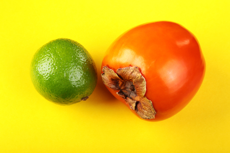 Fresh mixed exotic fruits lemon, persimmon and lime on a yellow background. Fruit background. Top View.