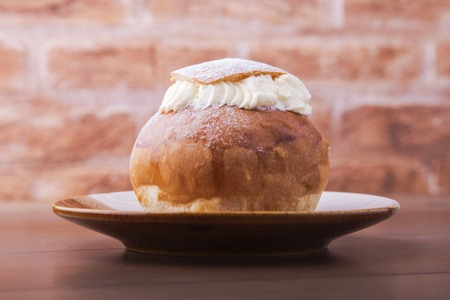 Traditional swedish dessert Semla, also called Shrove bun, with almond paste and whipped cream filling. Stock Photo