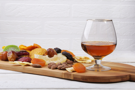 mix of dried fruits and nuts on a dark wood background. tinting. selective focus. Reklamní fotografie