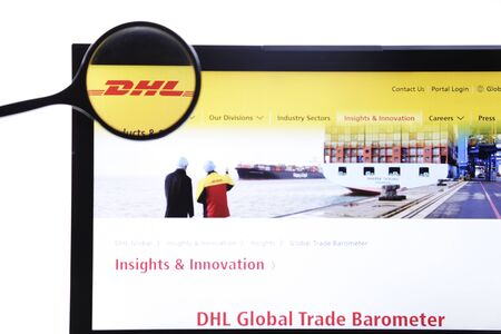 Berlin, Germany - April 1, 2019: Illustrative Editorial of DHL homepage on a monitor screen through a magnifying glass.