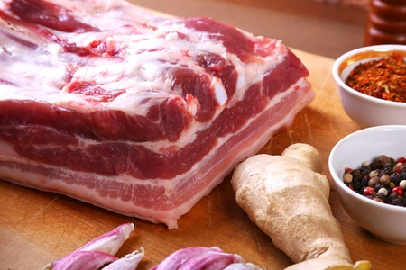 Raw fresh meat, uncooked lamb or beef ribs with pepper, garlic, salt and spices on dark stone background, Ready for cooking. copy space. Stock Photo