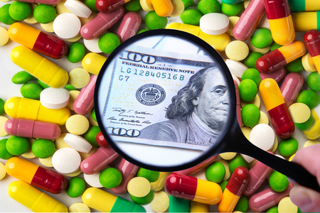Many expensive tablets or capsules under a magnifying glass turn into money, symbolizing paid expensive drugs and corruption. Medicine, health and payment concept.