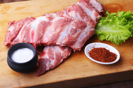 Raw Ribs on a rustic cutting board with salt, pepper and grinder for spices . copy space. Top View.