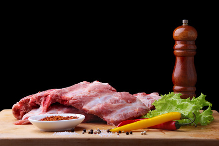 Raw Ribs on a rustic cutting board with salt, pepper and grinder for spices Banco de Imagens