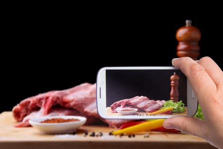 Hands of man with smartphone taking photo Raw Ribs on a rustic cutting board with salt, pepper and grinder for spices