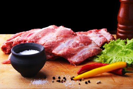 Raw Ribs on a rustic cutting board with salt, pepper and grinder for spices Stock Photo