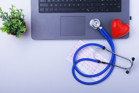 Workplace of doctor with laptop, stethoscope, RX prescription, glasses and red heart and notebook on white table. top view. Copy space.