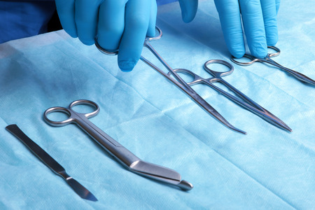 Detail shot of sterilized surgery instruments with a hand grabbing a tool