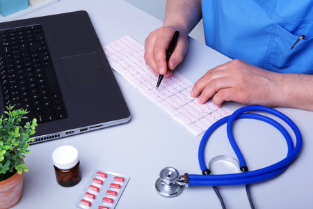 Close-up of doctors hands writing prescription and holding bottle with pills. Banque d'images - 124934746
