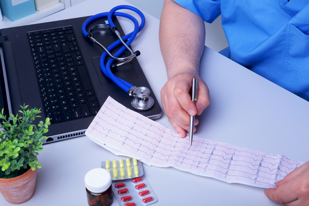 Close-up of doctors hands writing prescription and holding bottle with pills. Banque d'images - 124934750
