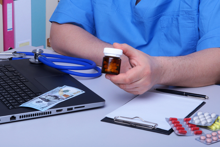 Medical concept - health price. dollars with assorted pills, cardiogram rx and stethoscope.