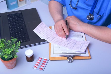 Close-up of doctors hands writing prescription and holding bottle with pills. Banque d'images - 124934754