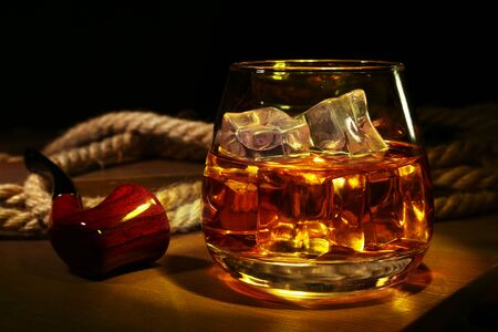 Glass with whiskey, ice cubes and smoking pipe on wooden Reklamní fotografie