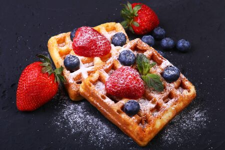 Homemade Traditional belgian waffles with fresh fruit, berries and sugar powder on black plate. Flat lay, top view, copy space.