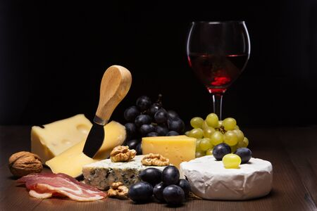 Assorted cheeses, nuts, grapes, fruits, smoked meat and a glass of wine on a serving table. Dark and Moody style. Free space for text. Stockfoto