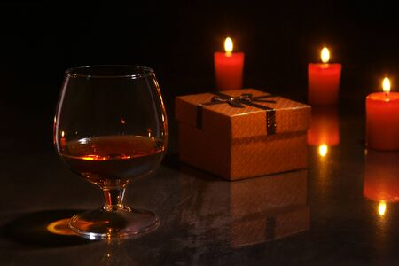 christmas decoration. glass of cognac or whiskey, red candles and gift box on a wooden background.