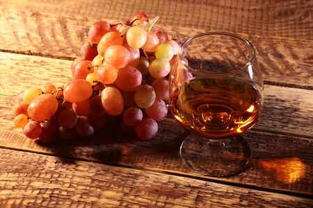 Cognac or Brandy in a glass and fresh grapes, still life in rustic style, vintage wooden background, selective focus