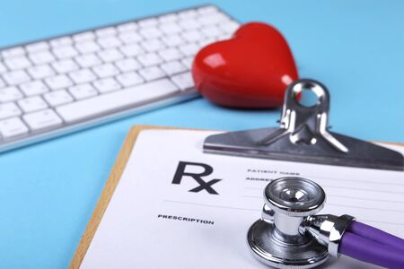 Medical stethoscope and red heart lying on cardiogram chart closeup. Medical help, prophylaxis, disease prevention or insurance concept. Cardiology care. Stock Photo