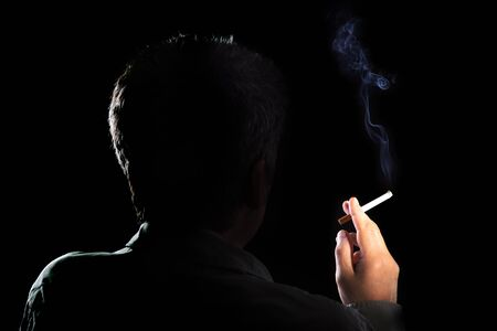 Mysterious man with cigarette and smoke isolated on a black background. Smoking kills. concept of the dangers of smoking. 版權商用圖片