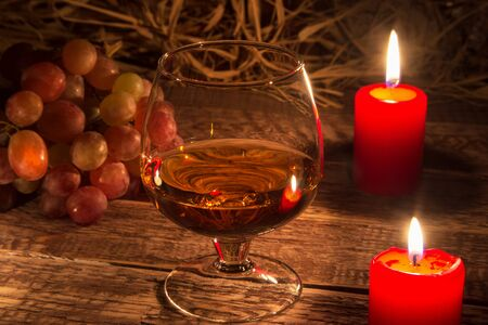 glass with brandy or cognac, grapes and candle on aged wood table background. Close-up view