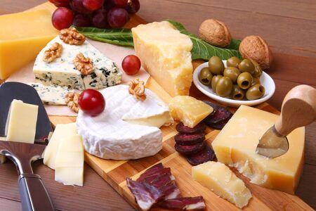 Surtido de queso con frutas, uvas, nueces y cuchillo de queso en una bandeja de madera