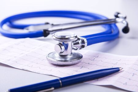 Medical stethoscope lying on cardiogram chart closeup. Medical help, prophylaxis, disease prevention or insurance concept. Cardiology care