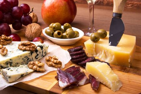 Assortment of cheese with fruits, grapes, nuts, glass with wine and cheese knife on a wooden serving tray