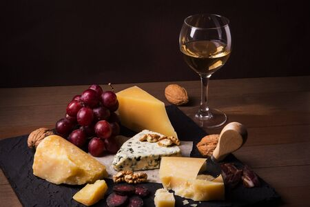 Assorted cheeses, nuts, grapes, fruits, smoked meat and a glass of wine on a serving table. Dark and Moody style. Free space for text Archivio Fotografico