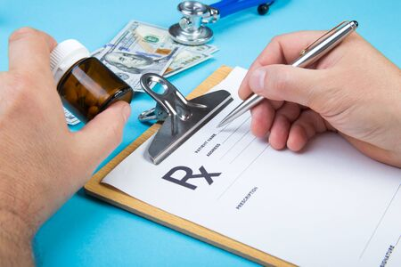 Male doctor or pharmacist holding jar or bottle of pills in hand and writing prescription on a special form. medical costs and healthcare payment concept.
