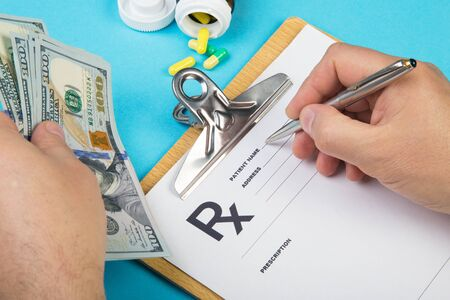 Male doctor or pharmacist holding money in hand and writing prescription on a special form. medical costs and healthcare payment concept. Archivio Fotografico