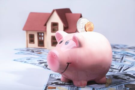 Real estate or home saving. piggy bank with coins on blur background money and house Archivio Fotografico