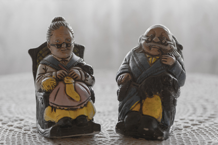 Porcelain figurines of a grandfather and a grandmother sitting
