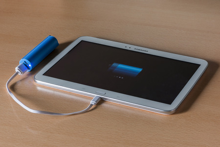 An external battery charging a white tablet