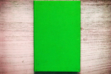 A book with the lid of a green color on gray background