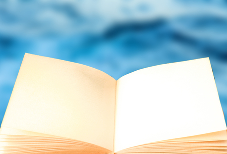 An open book with the blue sea in the background for graphic recourse