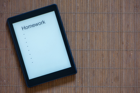 A black e-reader with white screen and text homework Stock Photo