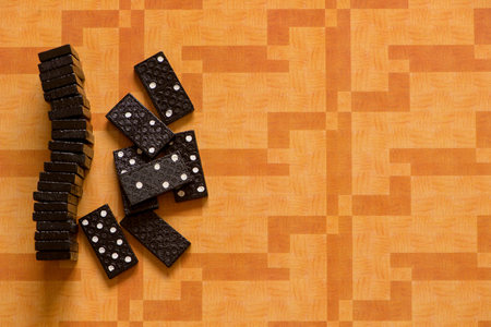 Small black dominoes on an orange background Stock Photo