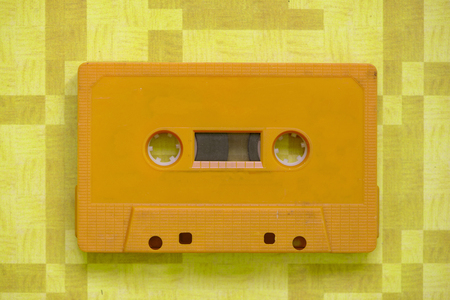 A retro cassette tape of a yellow color with orange background 版權商用圖片