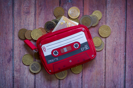 A purse with cassette shape and money on brown wooden table