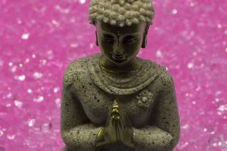 Small figure of buddha with pink diamonds in the background 写真素材