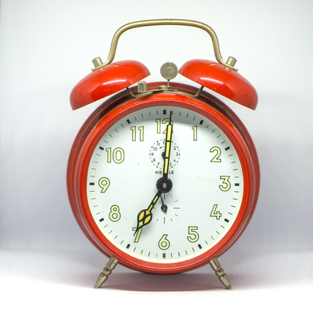 An old red alarm clock with white background