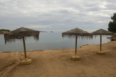 Umbrellas by the sea of Ibiza a cloudy day, Spain