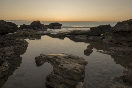 A sunrise between the rocks of Oropesa del Mar, Spain